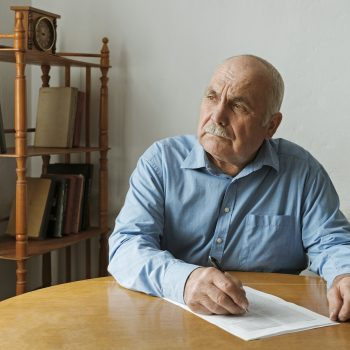 Old man writing notes or deciding whether to sign a paper document on the table in front of him as he looks to the side with a thoughtful engrossed expression